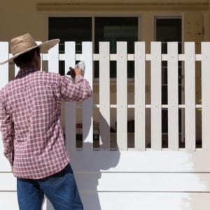 Man painting a fence white