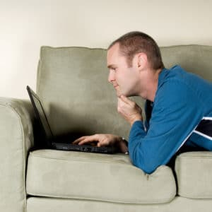 man with black laptop on green couch
