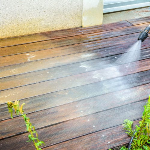 Pressure washer being used to remove Dilunett from a garden deck