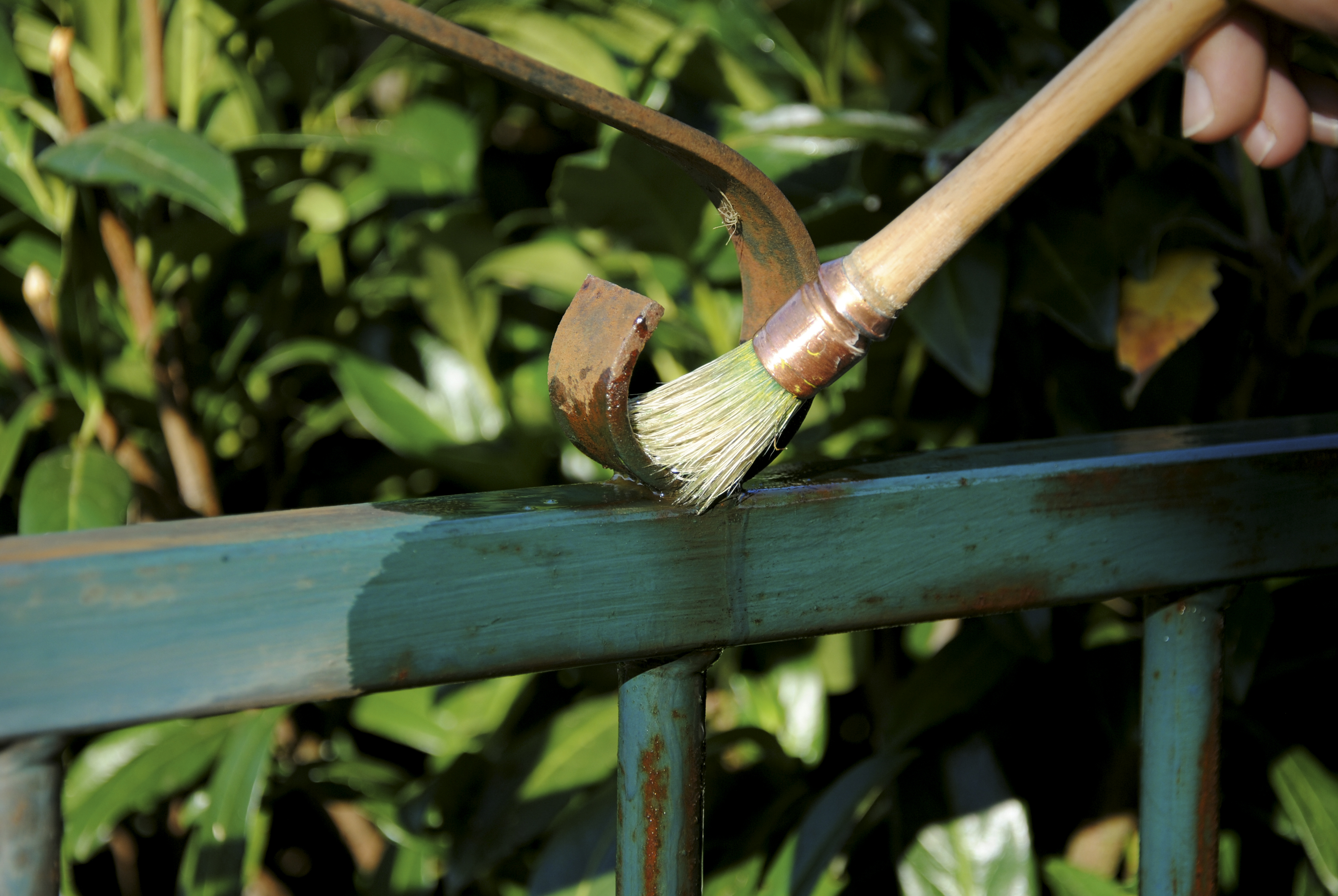 Owatrol Oil being applied to a rusted metal gate with a brush