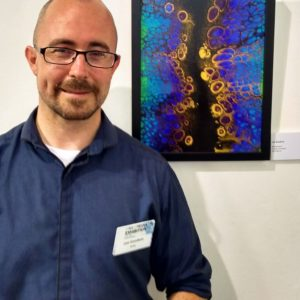Artist Lee Goodwin next to artwork made with Floetrol