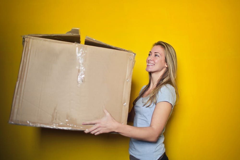 Woman holding large cardboard box