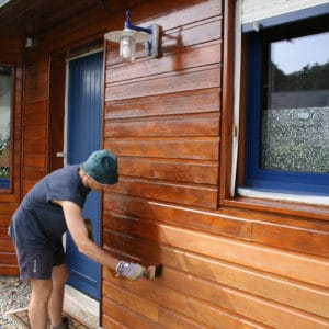 Man applying Linitop Classic with a brush to cladding