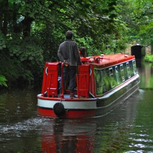 Man cruising a narrowboat towards a tunnel