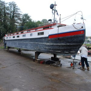 Narrow boat in a dry dock being blackened