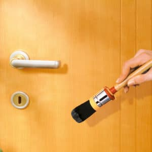 Linitop wood filler being applied to a wood door
