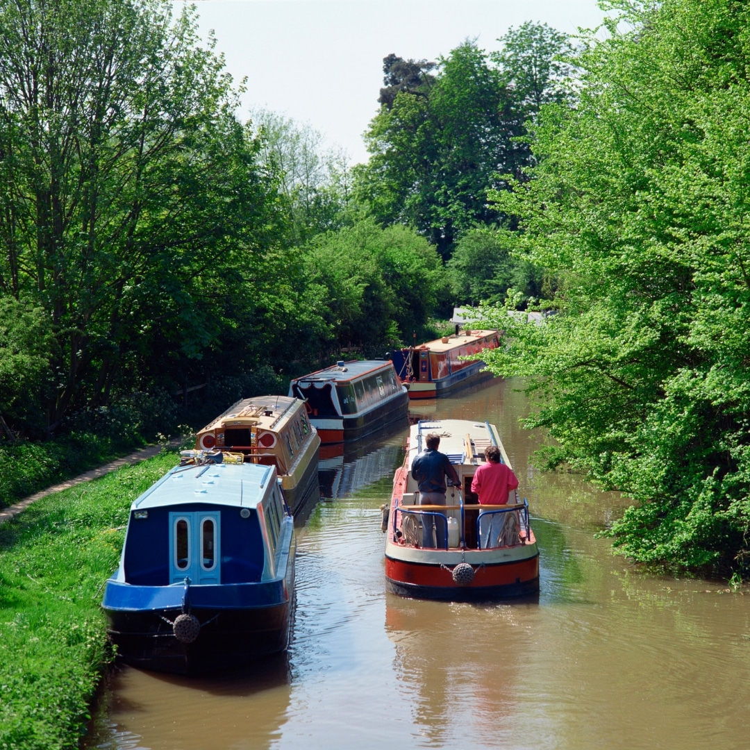 Hired out Narrowboat cruising alongside moored narrow boats