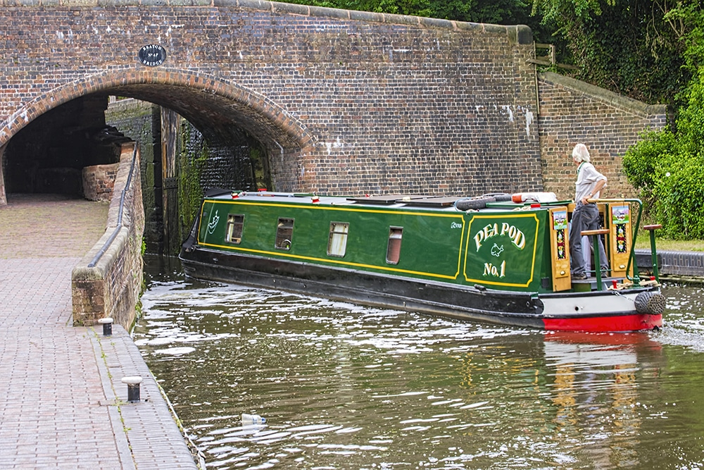 Man cruising a narrow boat under a bridge