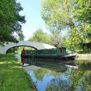 Green narrowboat cruising down a canal