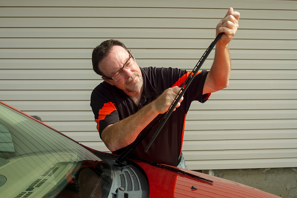 Man replacing wiper blades