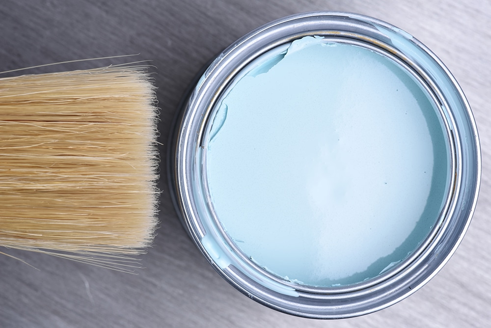 Light blue paint in a tin with a paint brush on top