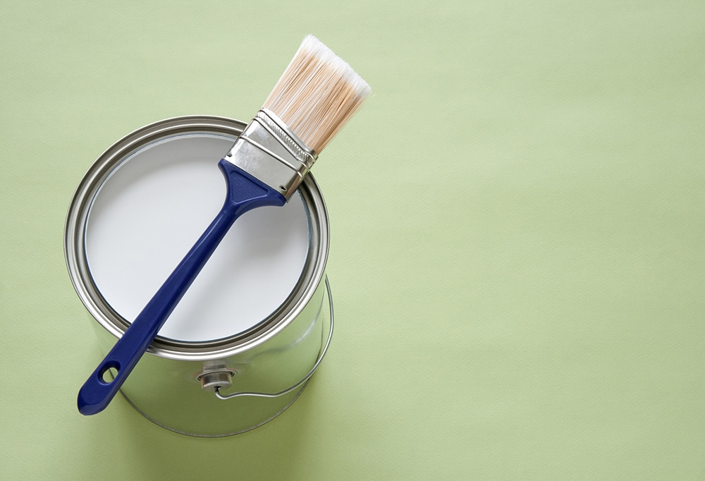 Paintbrush and a can of white paint