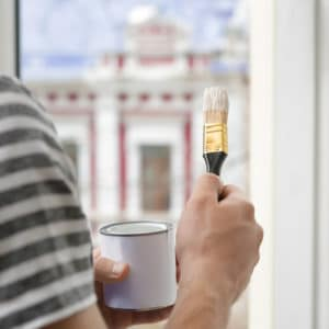 Man holding paint and brush