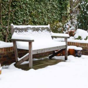 Garden bench covered in snow