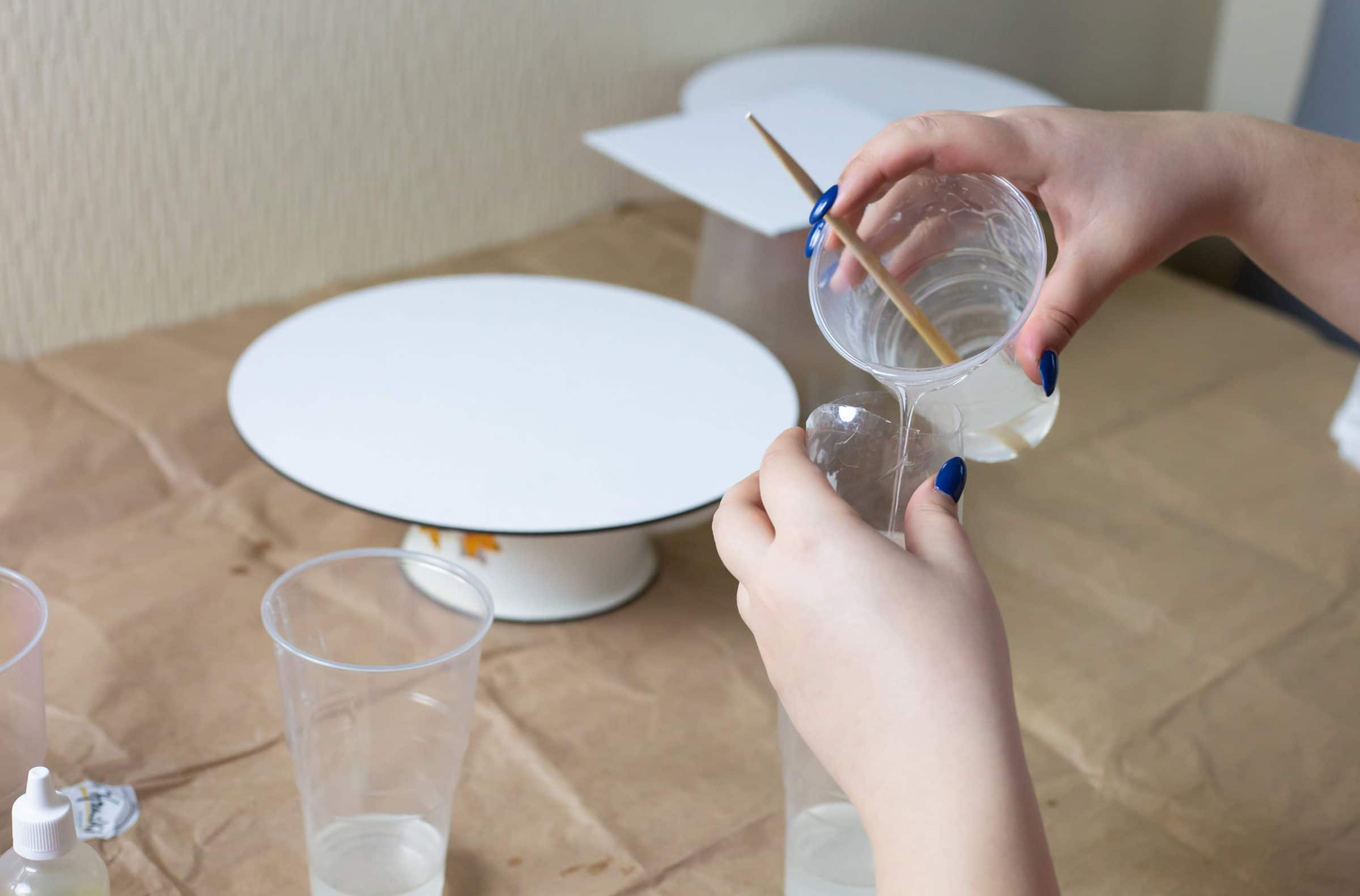 Pouring mixed resin into mixing cups