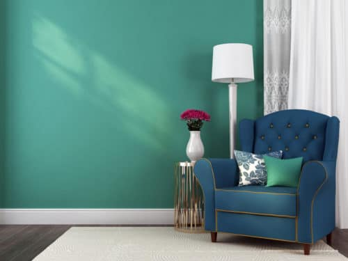 Blue armchair in front of a painted wall