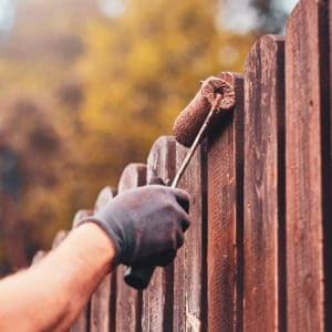 Person using a roller to paint a fence