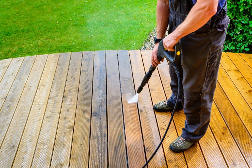 Before and after using a pressure washer on a garden deck